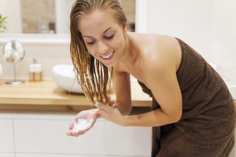 Femme appliquant de l'après shampoing